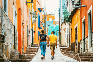 Couple holding hands while walking in a colorful neighborhood